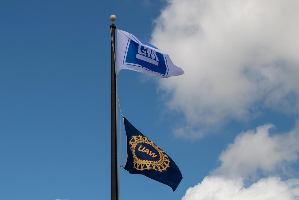 Flags for General Motors and UAW fly on a flagpole.