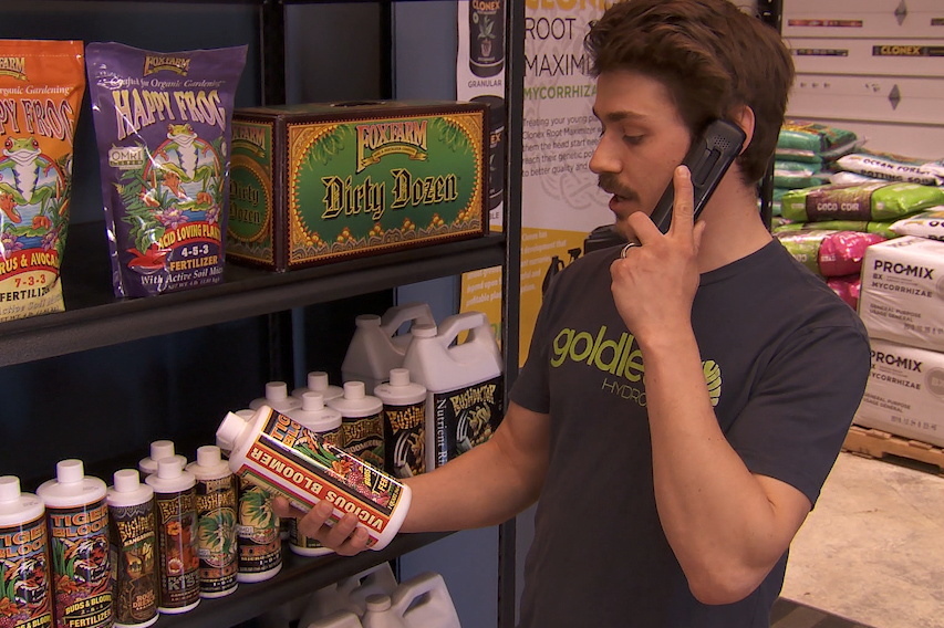 A photo of Goldleaf Hydroponics co-owner Kyle Billman talking on the phone with a customer.