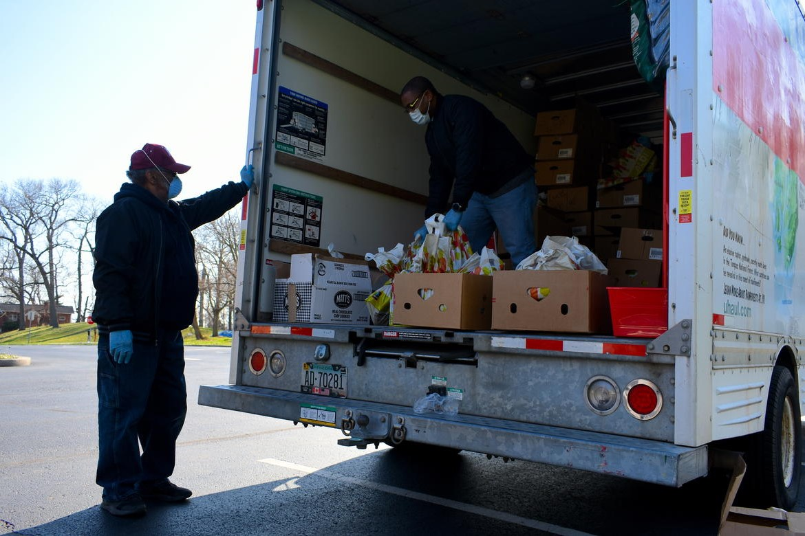 Church volunteers distribute free food out from a U-Haul truck in a parking lot.