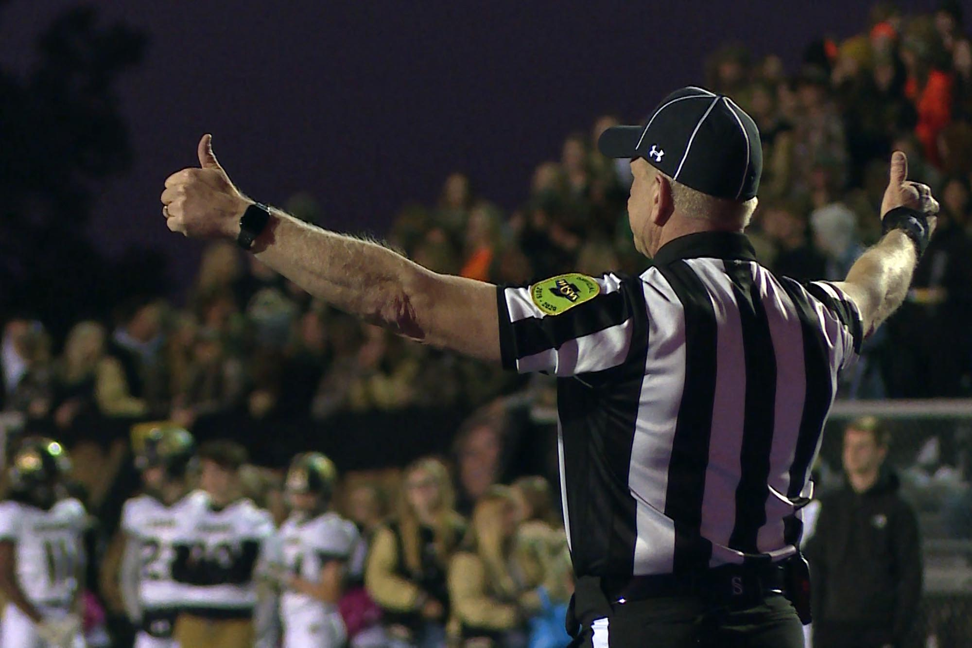 A shot of a high school football referee/official from the back.