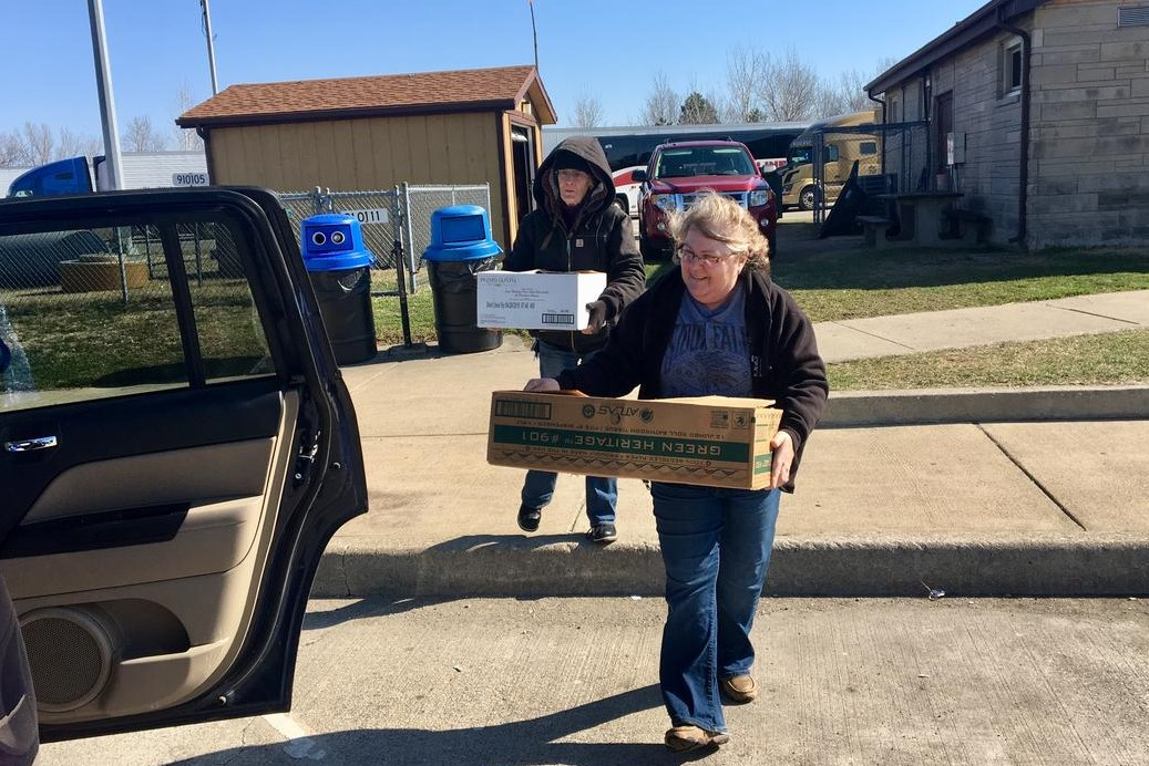 Wildlife rehabilitator Kim Hoover fills her car with pigeon-filled boxes.