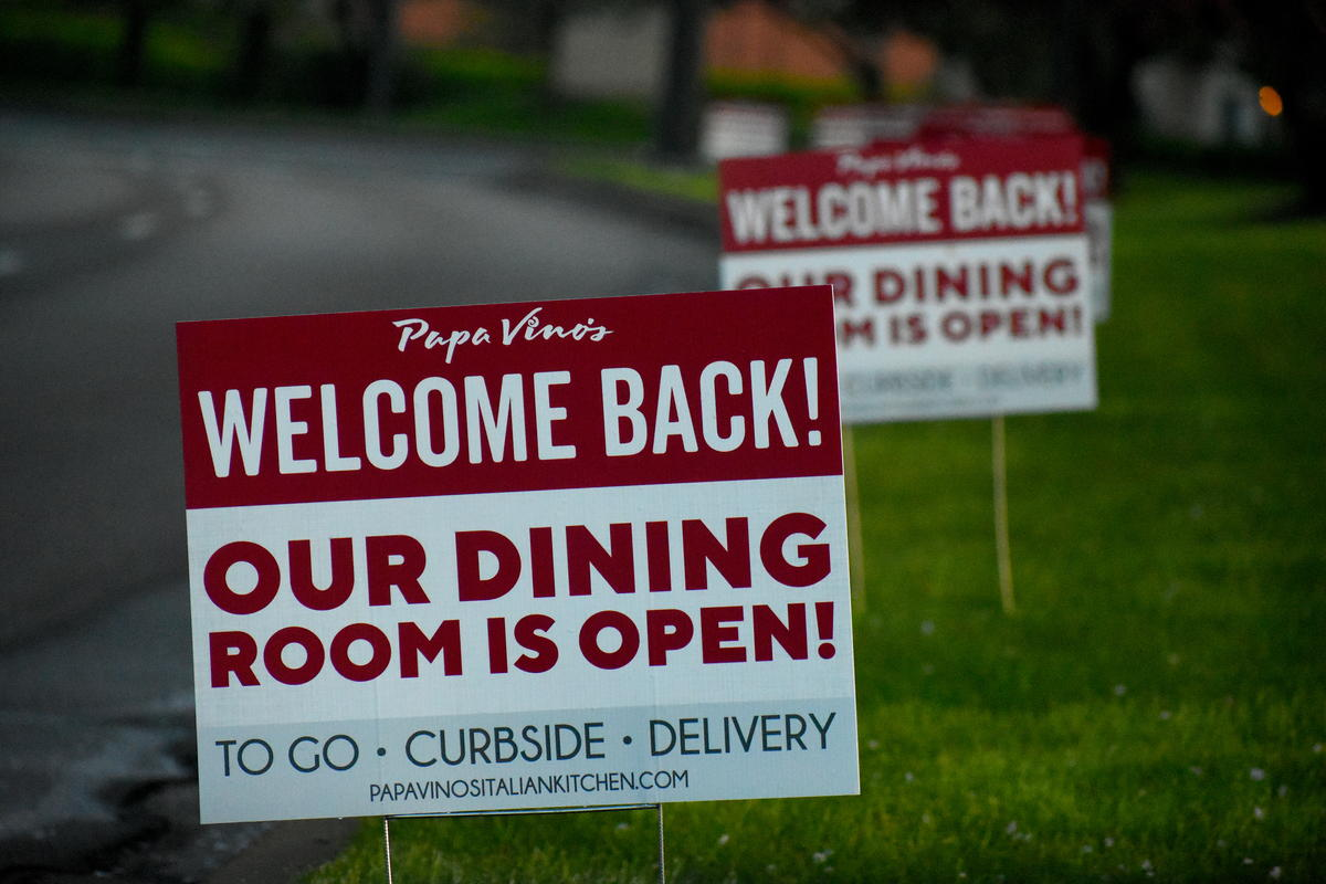 Signs advertising a restaurant reopening after local coronavirus stay-at-home restrictions are lifted.
