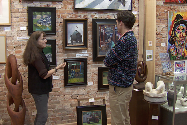 Juniper Art Gallery owner Jaime Sweany shows reporter Mitch Legan some of the artwork in her gallery on the town square