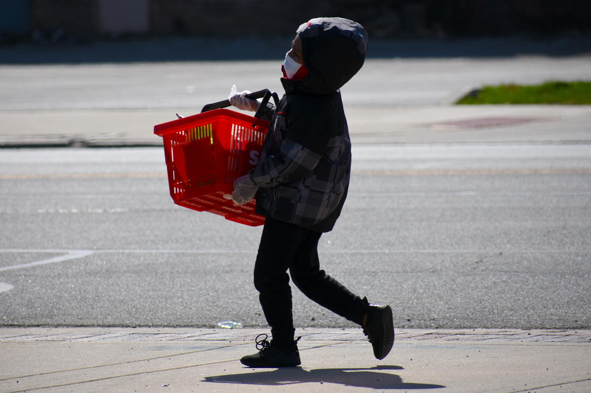 A child wearing a face mask and carrying a basket.