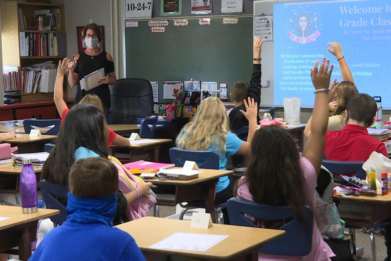 A classroom in a Logansport school, where the teacher is wearing a mask.