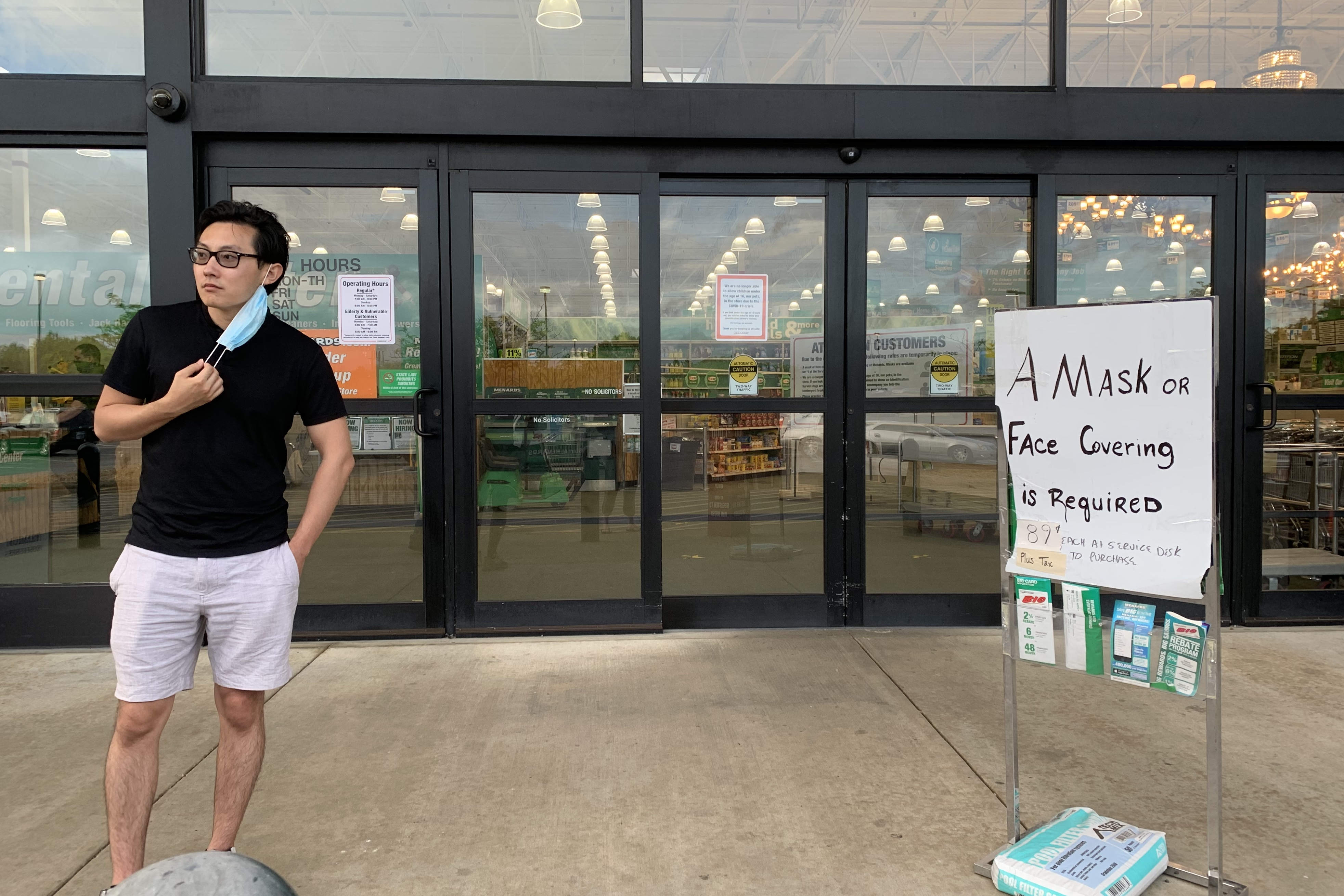 A man half-wearing a medical mask stands outside Menard's.