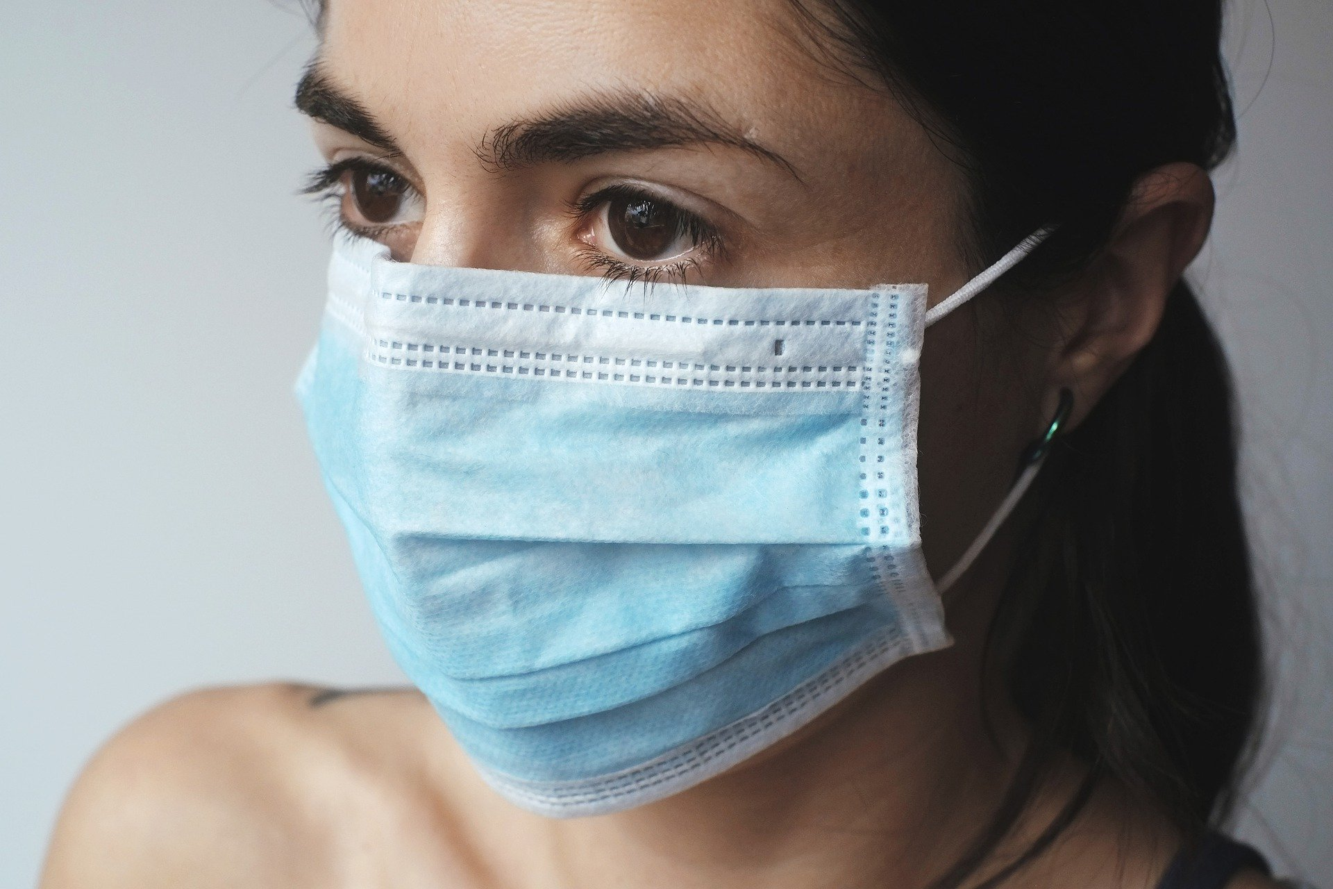 A stock image of a woman wearing a medical face mask.