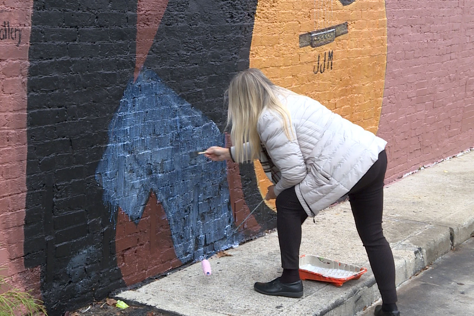 Pamela Bliss, mural artist, cleans up mellencamp's shoe, finishing her larger-than-life mural of him