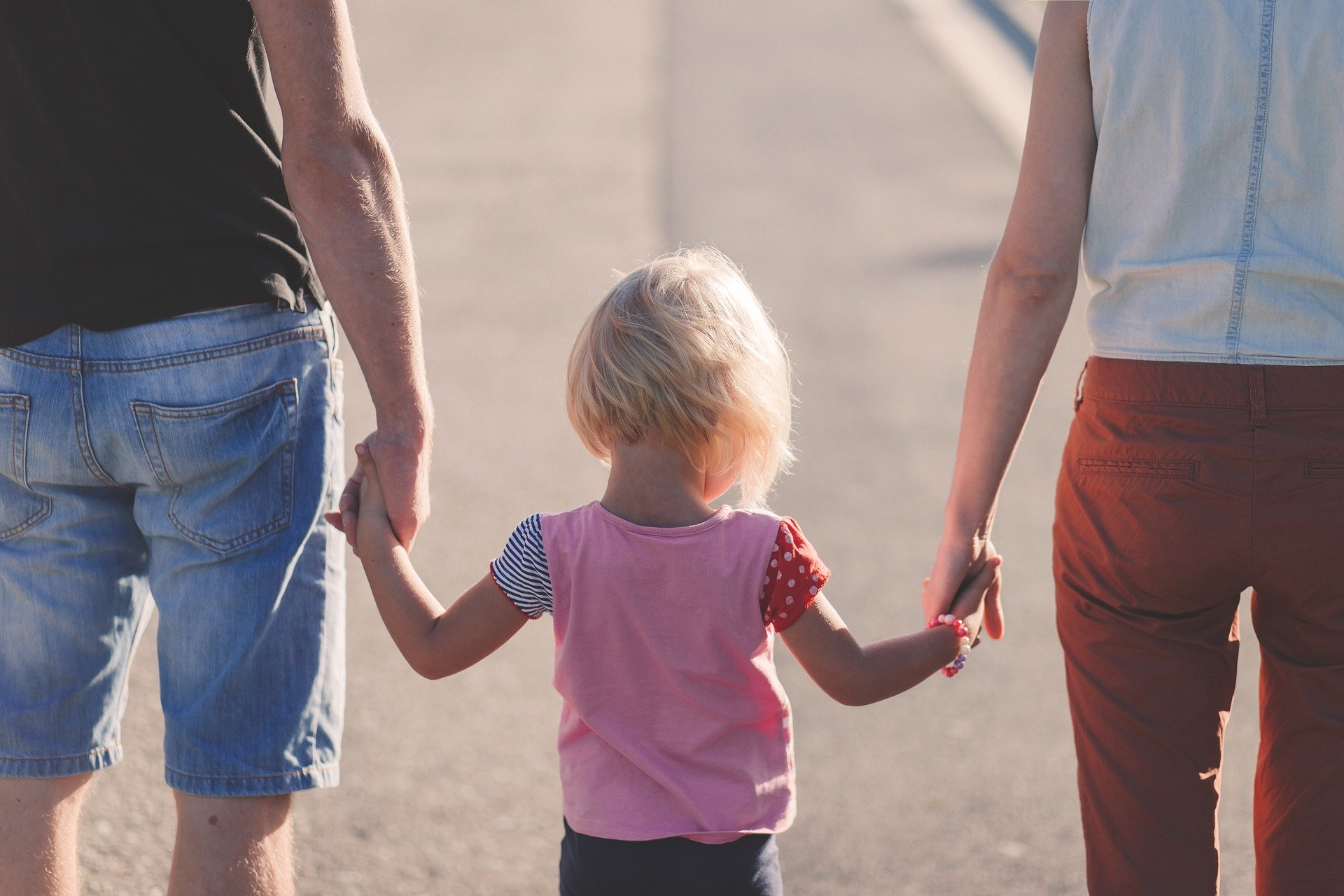 A child holding the hands of two adults (parents, divorce, parenting, kids).