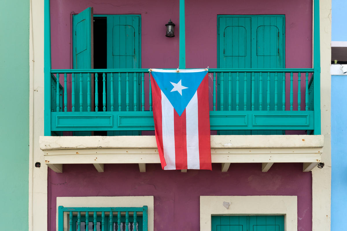 The flag of Puerto Rico hanging from a balcony.