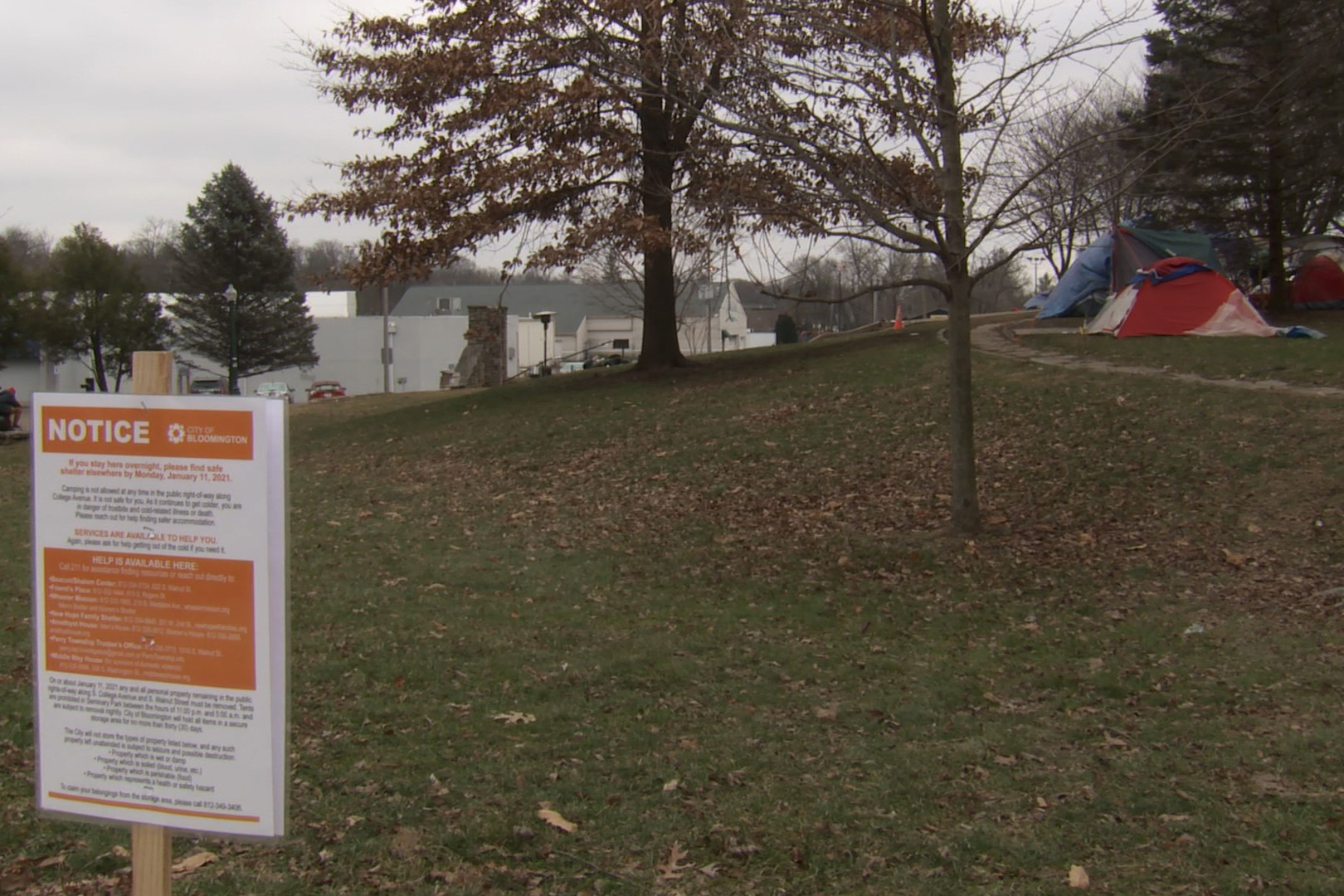 A photo of Bloomington's Seminary Park and a sign that says people must vacate.