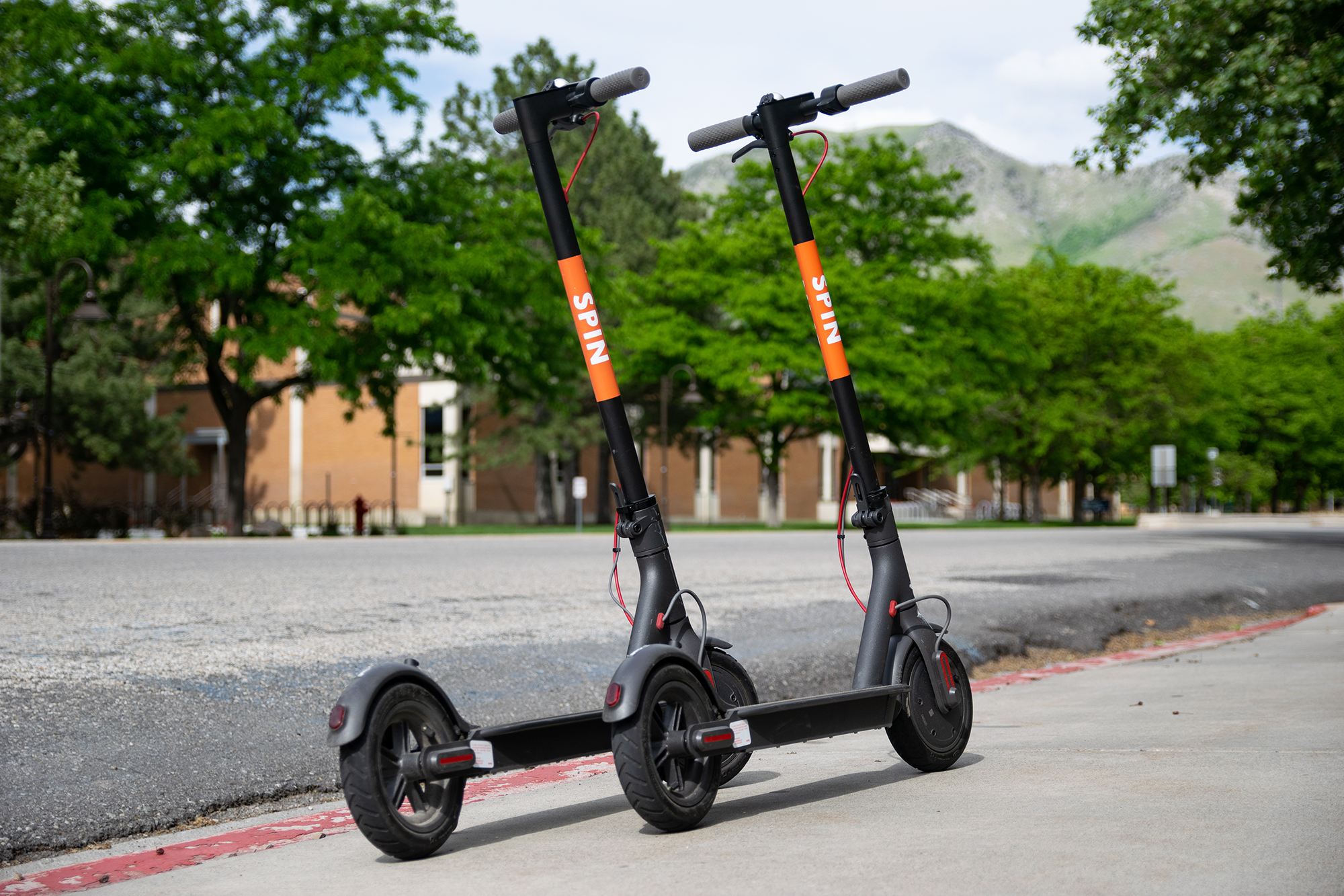 two orange and black spin electric scooters