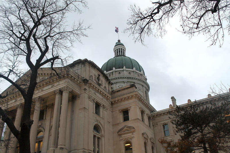 Indiana statehouse in winter with bare trees and gray sky