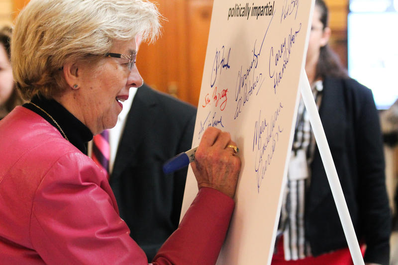 Rep. Sue Errington (D-Muncie) and other lawmakers sign a pledge to support redistricting reform