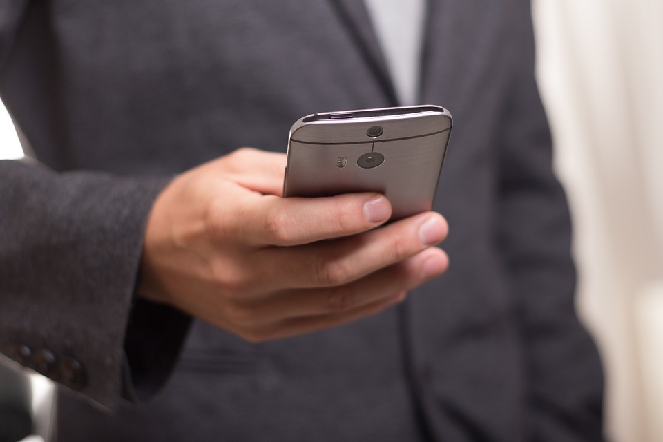 A stock image of a man holding a cell phone/telephone.