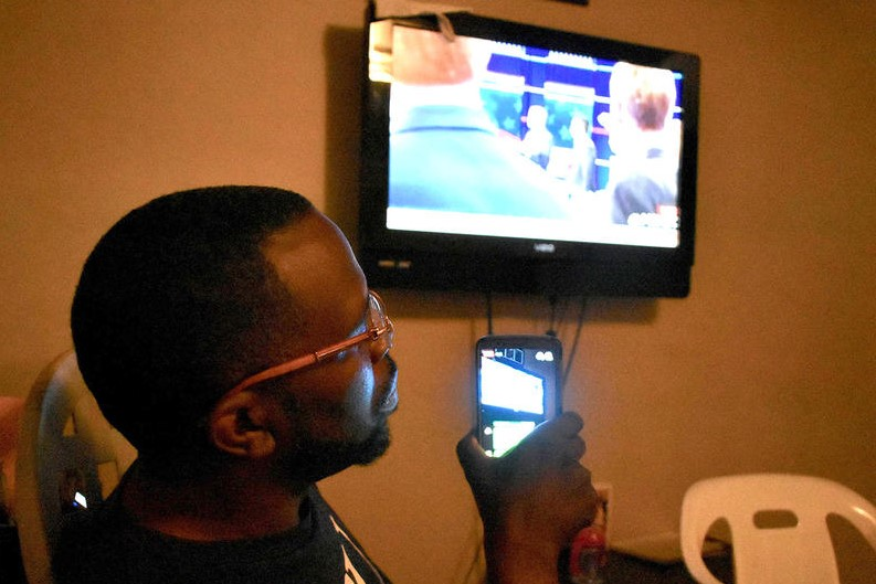 Vernado Malone streams the Democratic national debate on his phone at a watch party he organized for several South Bend activists.