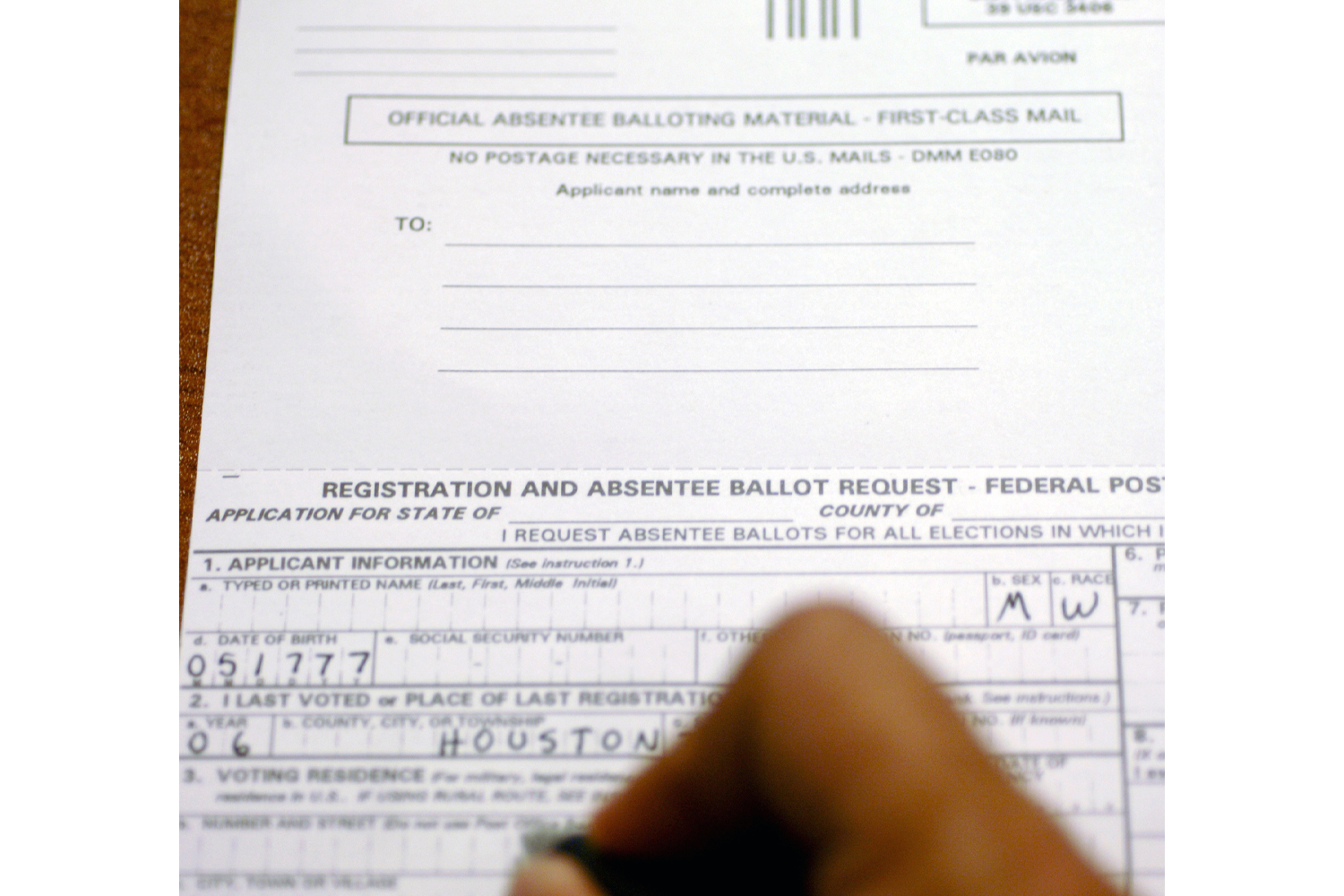 An image of someone filling out an absentee ballot/voting by mail.