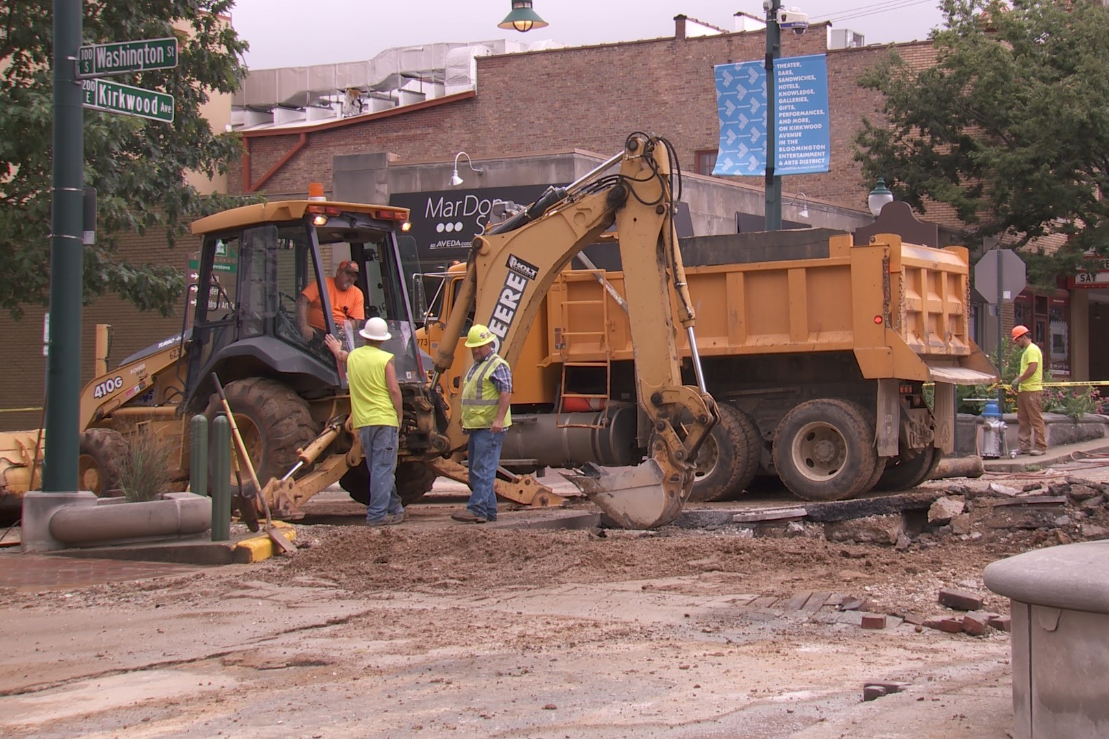 Construction workers operate a large digging mchine while fixing a water main break at the intersection of Washington and Kirkwood. July 2019.