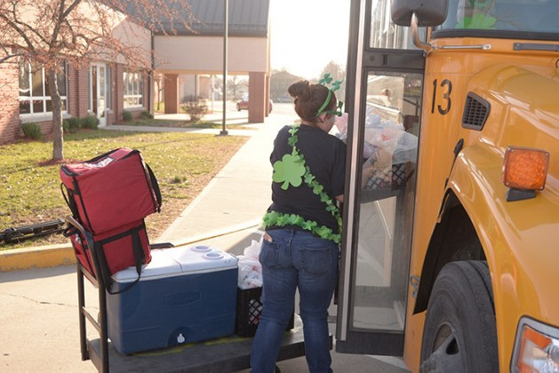A Wayne Township Schools staffer loads cold meals into a bus for distribution to students on Tuesday, March 17, 2020 at Rhoades Elementary