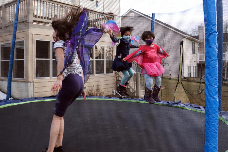 Kids wearing masks jumping on a trampoline.