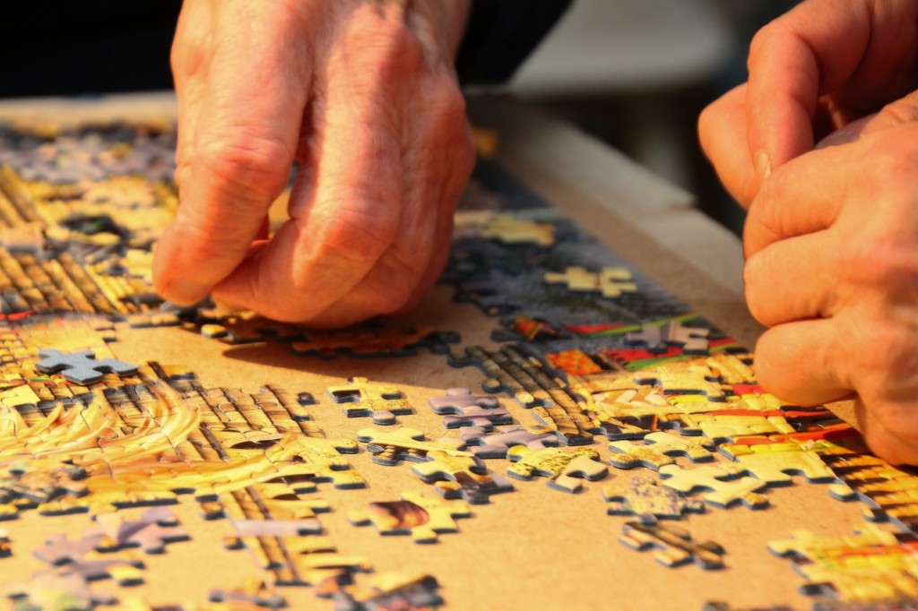 Peoples' hands putting together a jigsaw puzzle