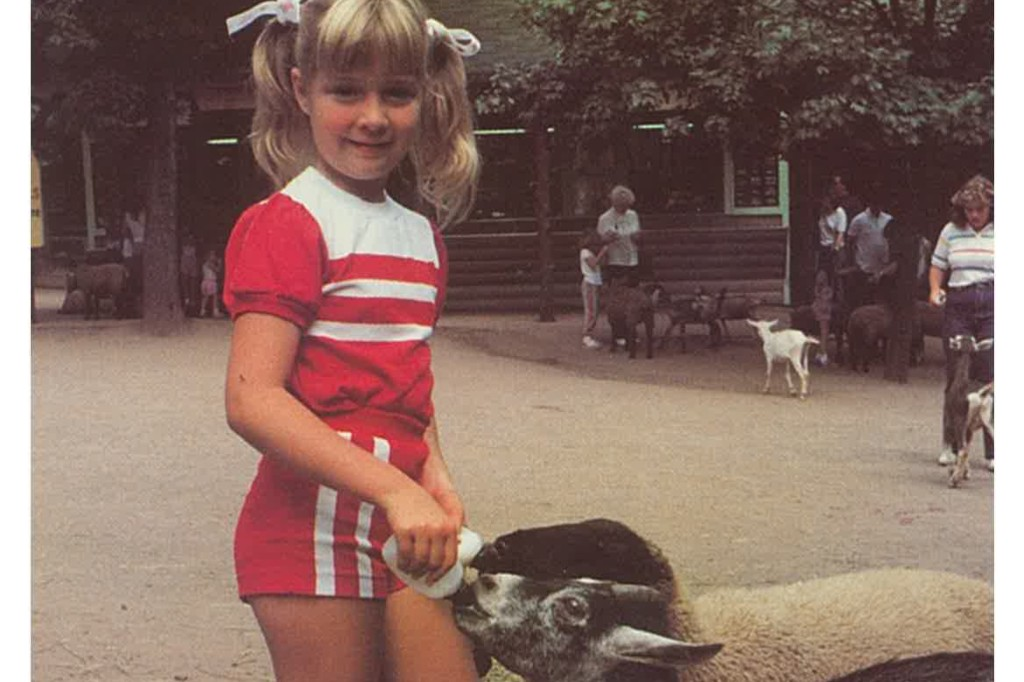 Young girl with pony tails feeding baby sheep with a bottle.