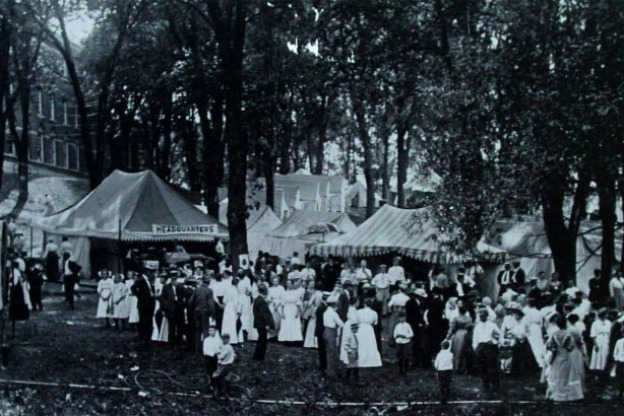 early 20th century photo of people under and next to white awnings at an outdoor gathering