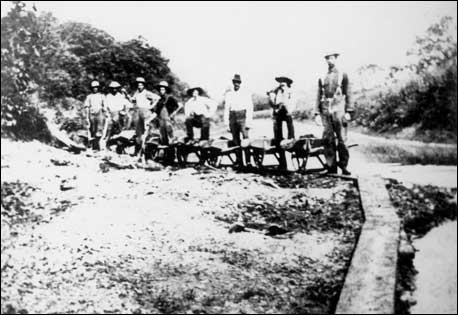black and white photograph of workers standing along canal