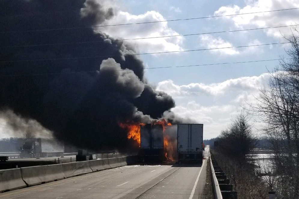 Two semi trailers on a two-way highway engulfed in flames