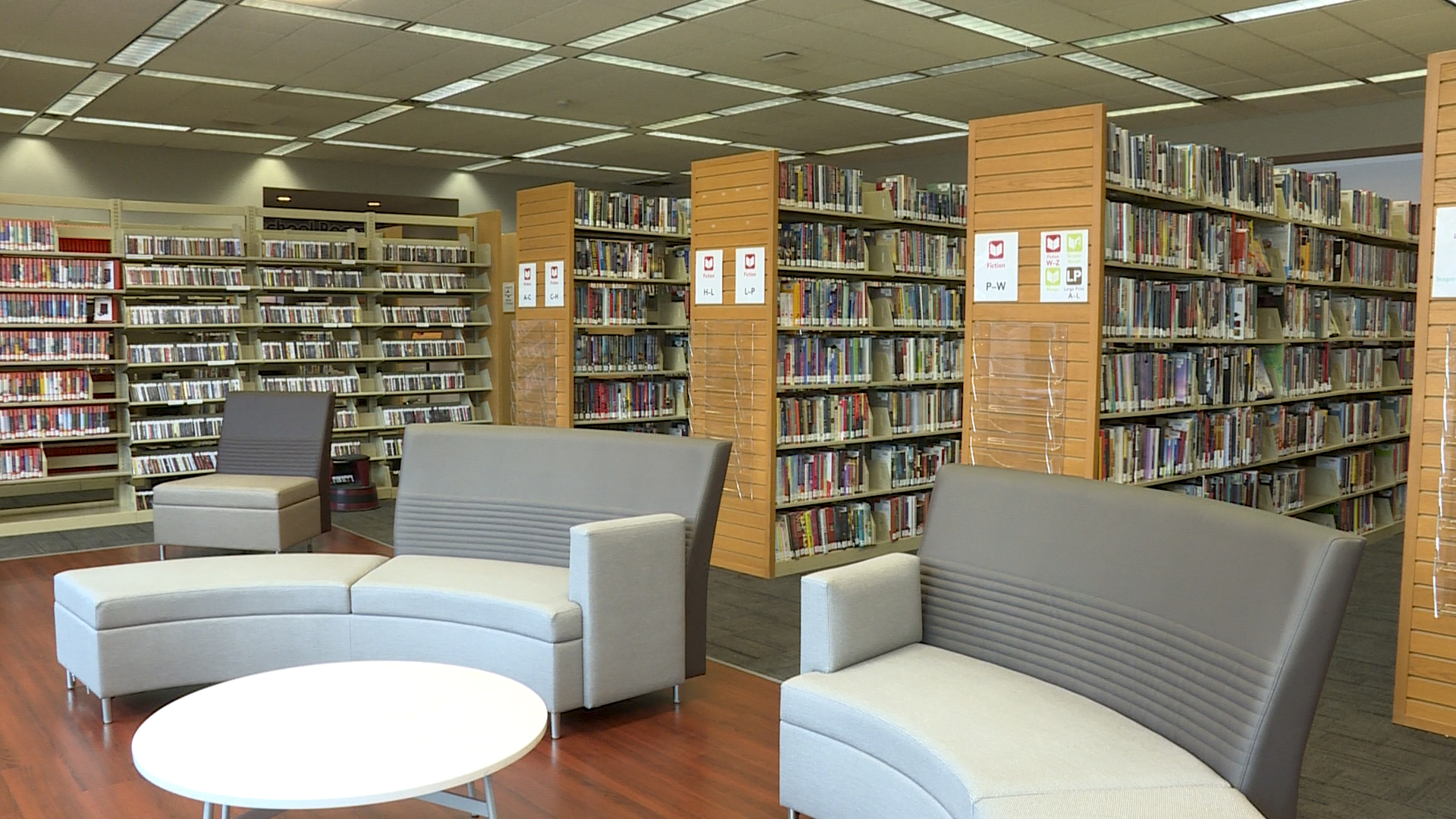 a library with shelves of books and tables