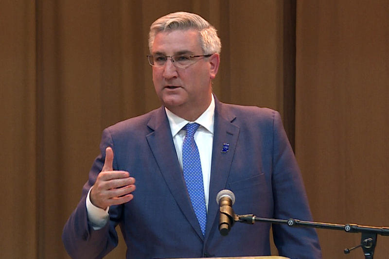 Governor Eric Holcomb at a podium in a blue suit and blue tie.