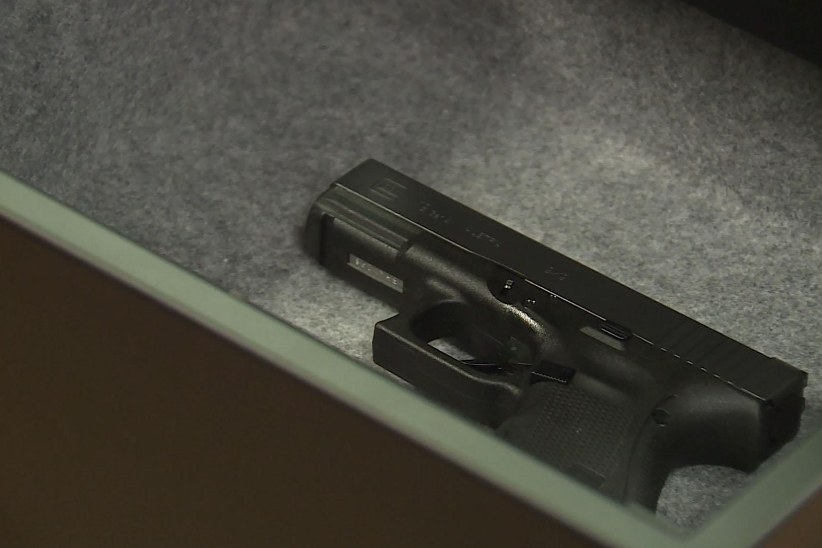 A handgun in a gray-lined gun safe.