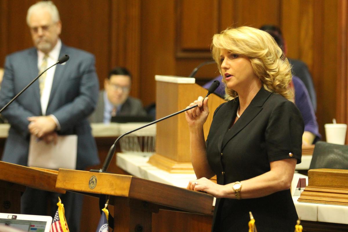 Rep. Karlee Macer at a podium at the statehouse