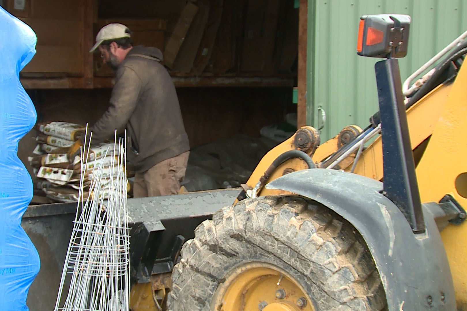 A man in a brown jacket works in a green shed with a tractor in front.