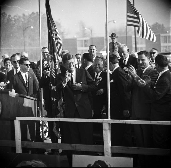 John Fitzgerald Kennedy to left of pole at center, and Birch Bayh to right of pole at center.
