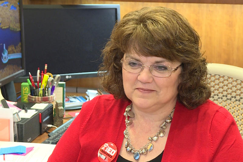 Teresa Meredith in a red shirt seated at her desk