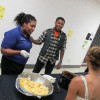 Tamika Riggs, who runs the after school program at Washington, serves dinner to students.