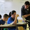 Our Lady teacher Matt Szumski assists a student reading during his social studies class.