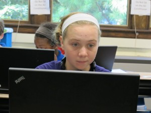 A seventh grader works on a laptop owned by her school in the classroom.