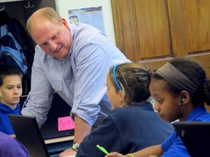 Teacher Troy Cockrum talks with students as they write papers on their school-owned laptops. Cockrum says the flipped classroom allows him to lay out multiple assignments at once and let students tackle the workload at their own pace.