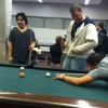 Sophomore Ricky Rojas (right, with pool cue) lines up a shot during a pool game with friends at IUPUI's Student Center. He says he's not sure if he would take advantage of summer courses where the tuition is cheaper.