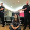 A protestor sits on the floor as Indiana University police officers monitor roughly two dozen people, mostly students. They were occupying a meeting of the IU Trustees on the Bloomington campus.