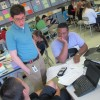 "Evansville science teacher Brian Bennett speaks with students in his chemistry class. Students use district-provided laptops in-class. Outside of class, they watch video lectures Bennett records, allowing them to do their homework with Bennett's guidance in class — the so-called ""flipped"" model."