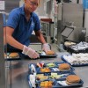 In this 2012 photo, a cafeteria worker prepares lunch trays for first grade students. (Elle Moxley/StateImpact Indiana)