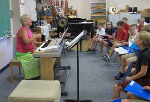 Choir teacher Kathy Gorr leads students at St. Charles Catholic School in Bloomington in a song.