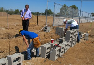 Gene Hack, director of C4 Columbus Area Career Connection, watches a commercial construction crew lay cement blocks for a dugout on Aug. 30, 2012. Students in the building trades program are working with professionals to build a new baseball stadium.