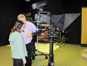 Don Baker, the TV instructor at Columbus East High School, shows a student how to run a camera. Students produce a live morning show at the end of first period each day that is broadcast at the school and throughout the community.