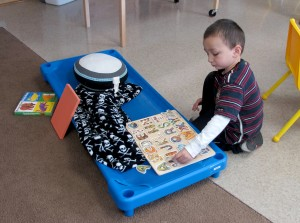 A student plays with an alphabet puzzle at Busy Bees Academy, a public preschool in Columbus.