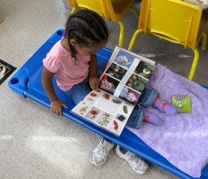 A student looks through a book about fruit and flowers at Busy Bees Academy, a public preschool in Columbus, Ind.