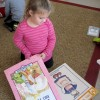 A student at Busy Bees Academy, a public preschool in Columbus, flips through books before story time.